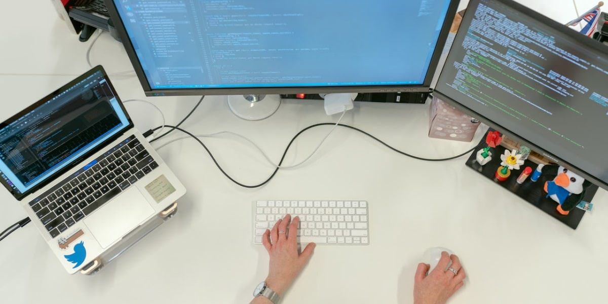 A web developer sits at two computer screens and a laptop, working with the Flask microframework