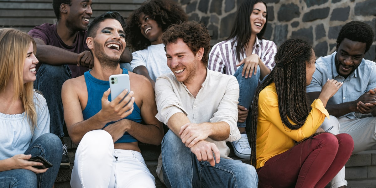Young group of friends sitting on steps using a smartphone and laughing.