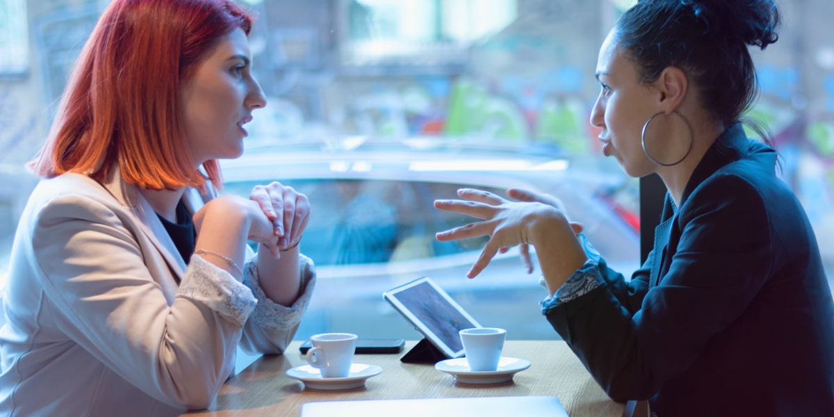 Two people sitting in a cafe, discussing the importance of a marketing portfolio